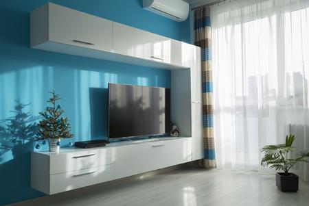 petit arbre de Noël décoré dans un seau sur les meubles dans le salon dans un intérieur agréable, à l'écoute dans les couleurs turquoise