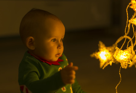 Santa helper baby on the floor decomposes Christmas lights that are shaped like stars