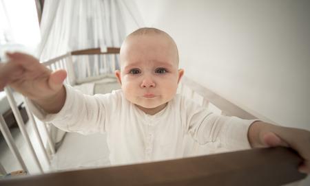 ojos tristes: pequeño bebé abandonado en la cuna llorando, estirando la mano para gran angular Foto de archivo