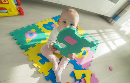 administered: baby playing with foam puzzle with his hand stretched out to us, wide angle