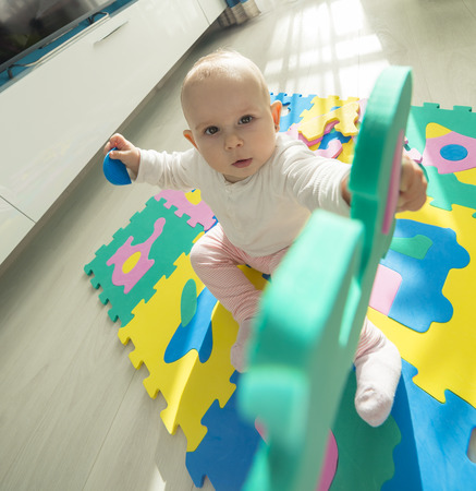 ''wide angle'': baby playing with foam puzzle with his hand stretched out to us, wide angle