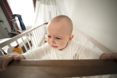 poco: pequeño bebé abandonado en la cuna llorando,