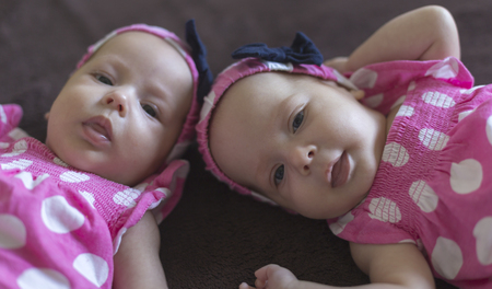 fraternal: Cute twins babatka with headband with ribbon and pink dress with white polka dots