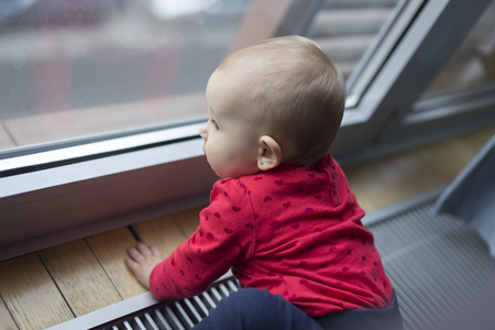 sad lonely child looking out the window in the rainy weather Foto de archivo