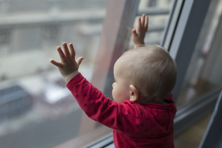 smutne samotne dziecko patrząc przez okno w deszczową pogodę z rękami na szybie