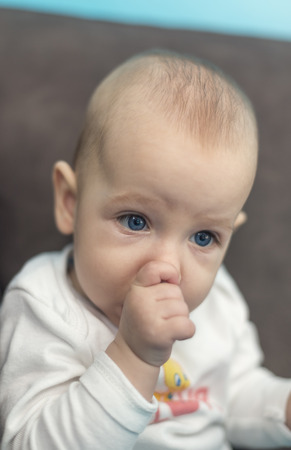 teats: baby with blue eyes sits and suck his thumb Stock Photo