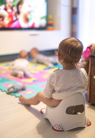Baby sitting on the potty in the living room and watch TV. With her sisters, twins Stock Photo