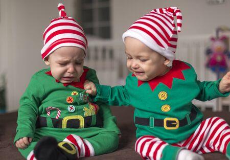 Aggressive children elf helper in Santa costume are fighting Stock Photo