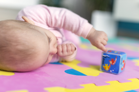 floor mats: adorable baby lying on Child-friendly, floor mats puzzle and suck his thumb