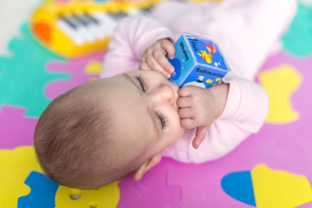 floor mats: adorable baby lying on Child-friendly, floor mats puzzle and bites into the foam cubes Stock Photo