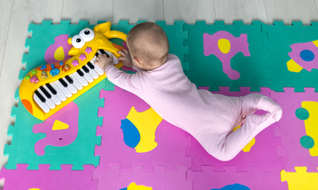 adorable baby lying on the floor Suitable for children puzzle carpet and playing the keyboard