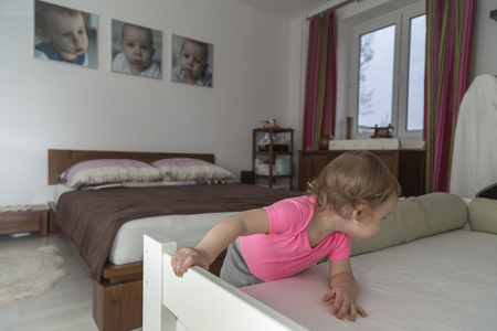 biased: The child climb into bed, three portraits of children hang on the wall,