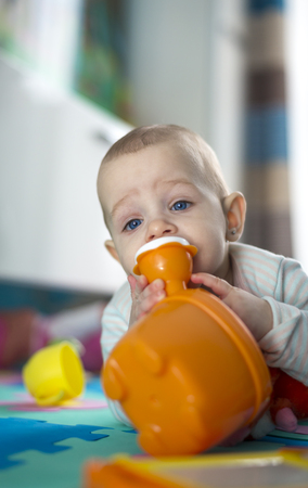 teether: Portrait of a little baby girl who eats, teething and hungry, chewing and playing toy Stock Photo