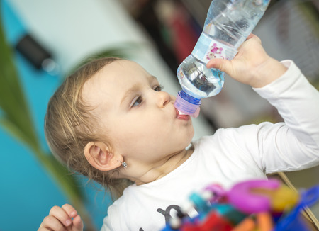 Adorable kid girl drinking water from bottle. Adheres to the drinking regime Stock Photo