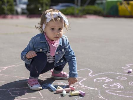 La piccola bella ragazza in una giacca jeans disegna con gessi colorati sul parco giochi