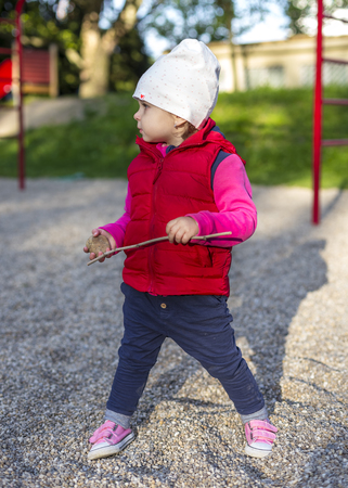 standing stone: Little girl pretty dressed playing on playground with stone and pestle Stock Photo