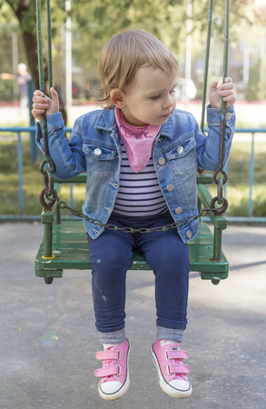 Beautiful little girl sitting securely chained on a swing