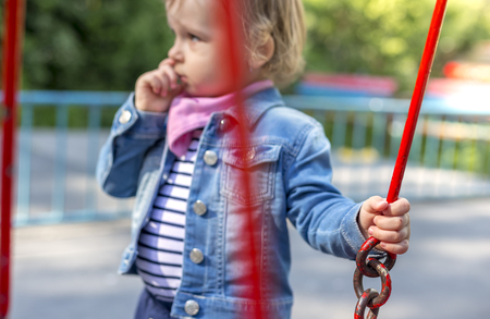 outoors: The unfortunate little girl on the playground, separated from the collective. Stock Photo