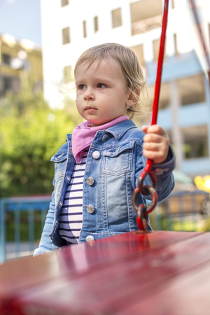 The unfortunate little girl on the playground, separated from the collective. Stock Photo