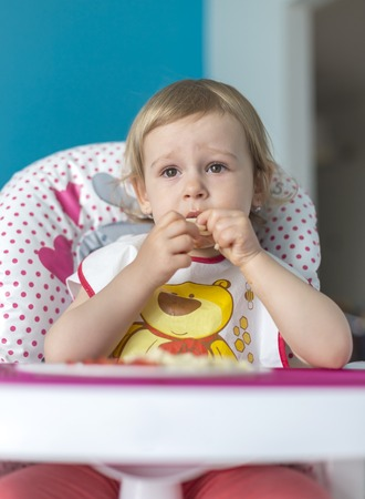 Baby breakfasts tomatoes with bread alone on highchair