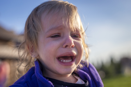 Little disheveled girl crying outdoors in the garden in front of the house Banque d'images - 100964342