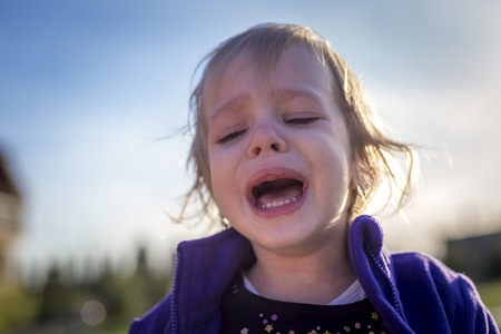 Little disheveled girl crying outdoors in the garden in front of the house