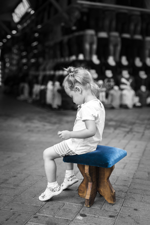 In Turkey on the markets girl, waiting in the street, sit on a Turkish stool 스톡 콘텐츠