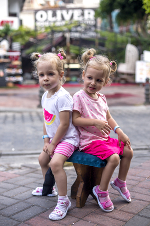 In Turkey on the markets two sisters twin, waiting in the street, you both want to sit on a Turkish stool 스톡 콘텐츠