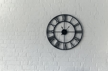 Vintage clock with Roman numeral. wall clock-face dialrustical on white brick wall in the apartment, Фото со стока