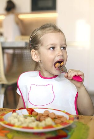 little girl  breakfasting  sausages at home behind a childrens table Imagens