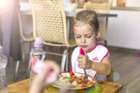 little girl  breakfasting  sausages at home behind a childrens table Stock Photo
