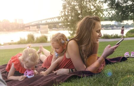 Mother with daughters having picnic by river, she chats on smartphone and not looking after children.
