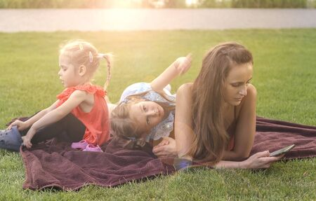 Mother with daughters having picnic by river, she chats on smartphone and not looking after children. Stock Photo