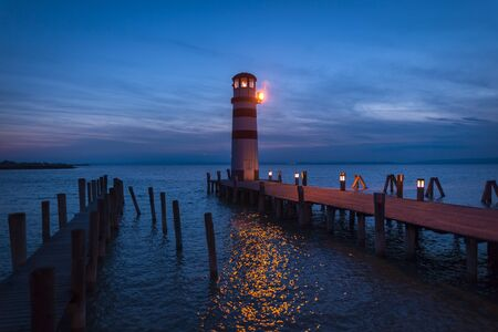 Lighthouse at Lake Neusiedl, Podersdorf am See, Burgenland, Austria. Lighthouse at sunset in Austria. Wooden pier with lighthouse in Podersdorf on lake Neusiedl in Austria. Stock Photo
