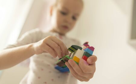 Cute funny preschooler little girl playing with construction toy blocks building and tower in a sunny kindergarten room. Kids playing. Children at day care. Child and toys.
