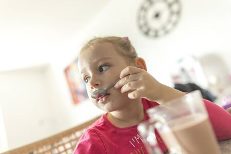 Little girl drinks cocoa at home in the kitchen behind the table