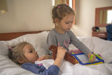 two little sisters lying in beds in a hotel room Stock Photo