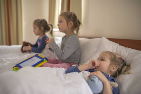 Three little sisters lying in beds in a hotel room