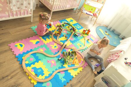 Girls play with a wooden set in their children's room on the floor. There are colorful puzzles on the floor.