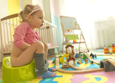 girl pushing on potty while playing in their children's room on the floor. There are colorful puzzles on the floor.