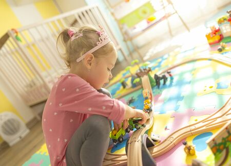 Girl play with a wooden set in their children's room on the floor. There are colorful puzzles on the floor. Stock Photo