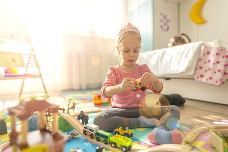 Girl play with a wooden set in their children's room on the floor. There are colorful puzzles on the floor.