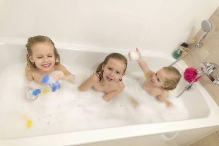 Glückliche Kindermädchen baden in einem Bad mit Schaum und Blasen.
