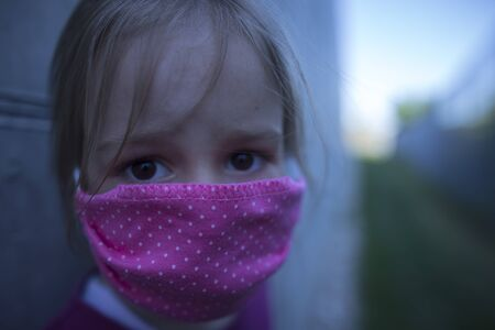 A child in Eastern Europe protecting himself from a coronavirus with a face mask. Fear in the eyes. Stock Photo