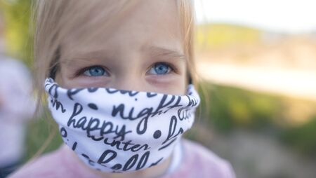 Happy child in Eastern Europe protecting themselves with a face mask from coronavirus. Slovakia Stock Photo