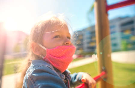 Happy children in eastern europe playing with face masks on playground during quarantine covid19. Slovakia Stock Photo