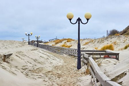 Sandy boardwalk. Lighting lights. Movement of dunes