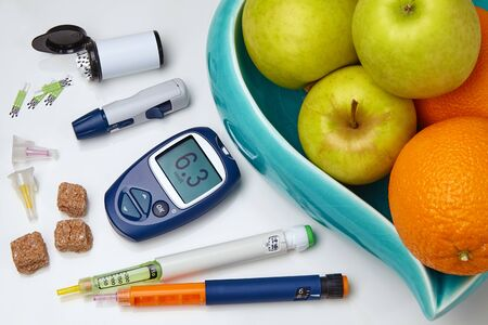 Glucometer, insulin syringe pen, sugar vase with apples and oranges on a white table. Diabetic nutrition concept
