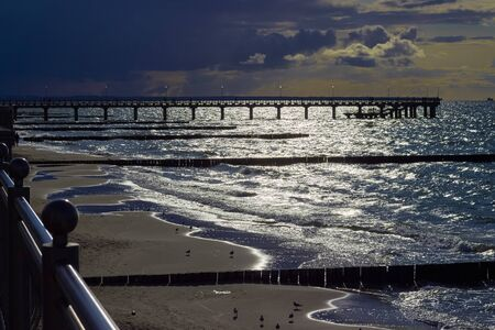 Boardwalk and breakwaters in the setting sun. Seagulls on the beach. Bright highlights and deep shadows.