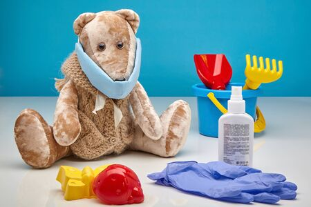 Teddy bear in a medical mask, latex gloves, an antiseptic and scattered childrens toys on a blue background